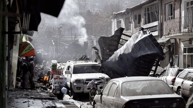 mangle structures blown halfway down a street, with debris all over the pavements and people crowding around a plume of smoke in the background