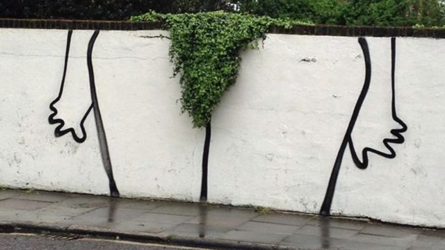Humorous graffiti in London shows the contours of legs around a bush overhanging a wall