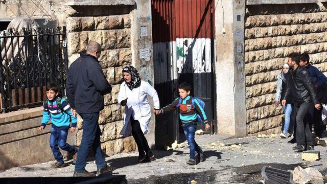 صورة أم تصحب طفليها من المدرسة