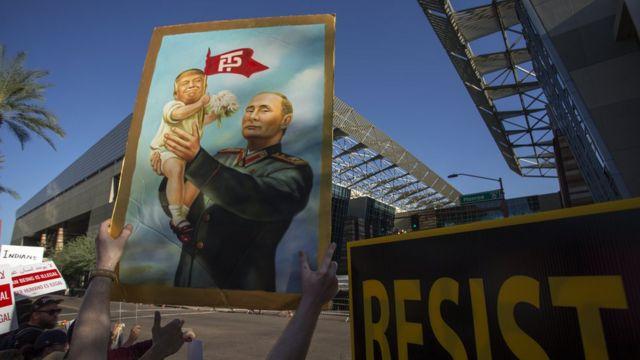 Плакат с Путиным в военном мундире, держащим на руках младенца-Трампа