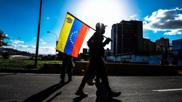 Pessoa segurando a bandeira da Venezuela