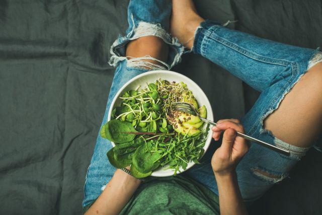 Тарелка с растительной пищей на коленях у девушки