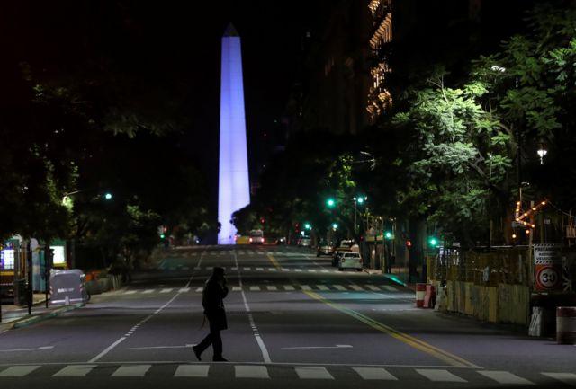 Una persona en una avenida solitaria de Buenos Aires con el Obelisco en el fondo