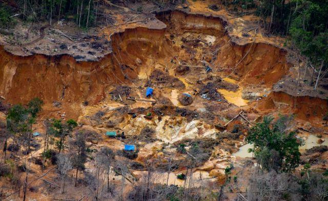 Foto aérea mostra grande buraco com poços no meio da floresta