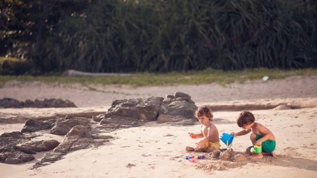 Duas crianças brincando na praia