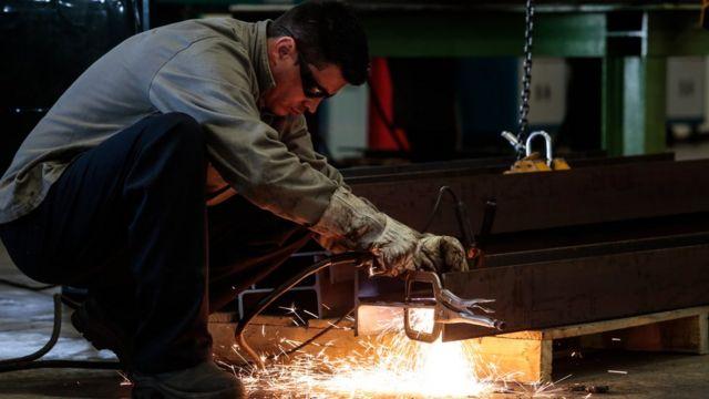 Homem trabalha em indústria brasileira