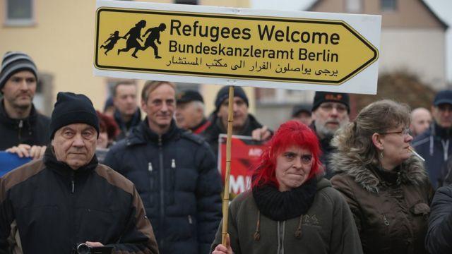 """Una mujer sostiene un cartel en una manifestación que dice: """"Bienvenidos, refugiados""""."""