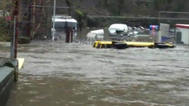 A bus is swept down a flooded street in Hebden Bridge