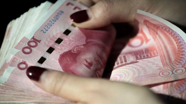Manos sosteniendo varios billetes de yuanes.