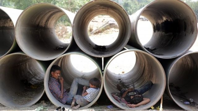 Indians rest in unused water pipes to avoid the heat on a hot summer day in New Delhi, India, 19 May 2016