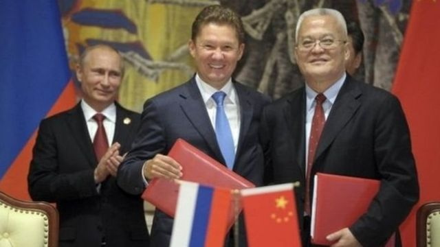 Gazprom CEO Alexei Miller (centre) and CNPC Chairman Zhou Jiping shake hands as Russian President Putin looks on during the signing ceremony in Shanghai