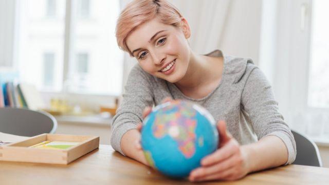 Una mujer sostiene un globo terráqueo.