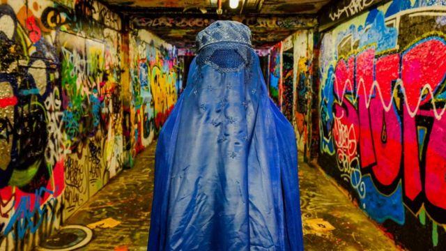 Grafittiler arasında burkalı bir kişi