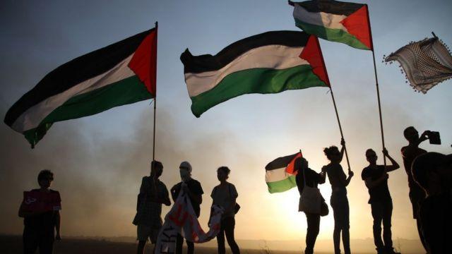 شباب يرفعون العلم الفلسطيني