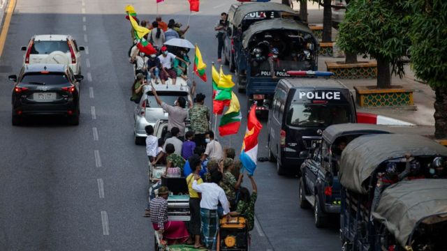 Military supporters drive-by police trucks parked aside the Streets in Yangon.