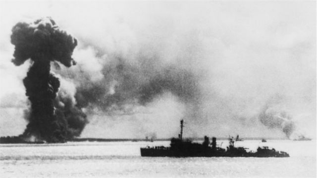 A Japanese air attack on Port Darwin, Australia, during World War II, 1942. In the foreground right is a US destroyer, and behind it (left to right) are the burning remains of an Australian ship, an Australian hospital ship and a British ship.