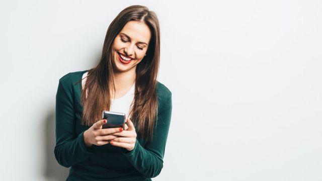 Una mujer escribiendo en un celular