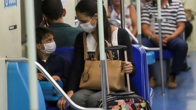 Pessoas usando máscaras no metrô