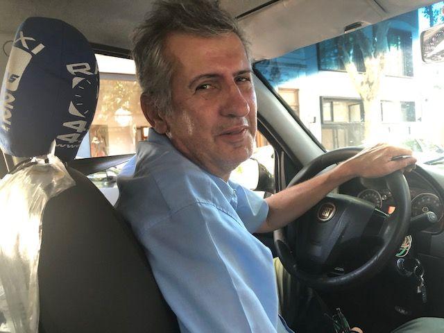 O taxista Marcelo Martínez posa para foto dentro do carro
