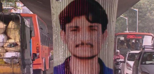Imagem mostra o trânsito de carros em rua da Índia e, no centro, um pilar com a pintura do rosto de Kaalu, homem de 26 anos que foi morto pela população após ser apontado como sequestrador - por causa de um vídeo falso que circulou no WhatsApp e deixou as pessoas em pânico.