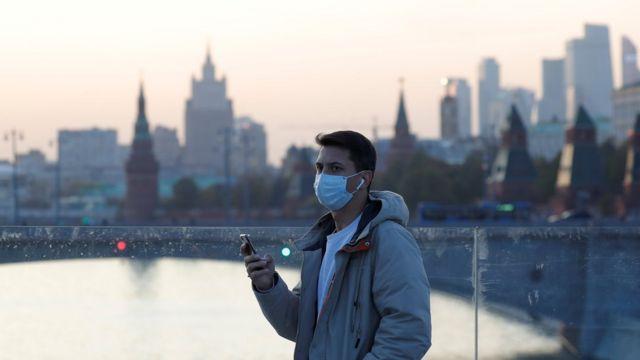 Мужчина в маске на мосту через Москву