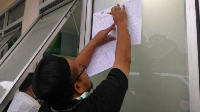 Anggota Tim DVI menempelka daftar jenazah korban tsunami yang sudah teridentifikasi di RS Berkah, Pandeglang (24/12).