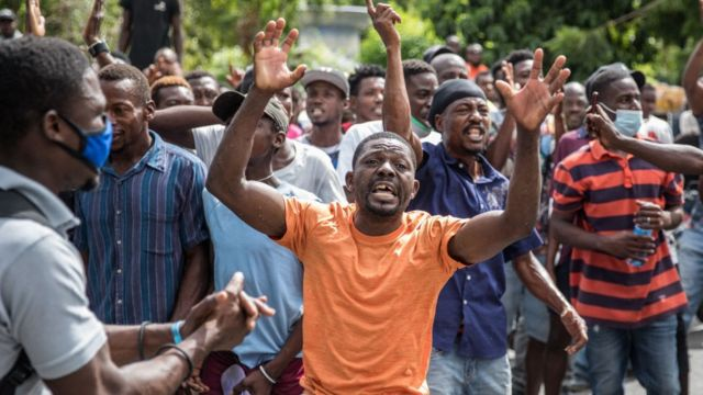 The crowd reacts near the Police station where armed men are being detained
