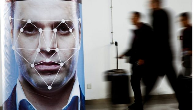 A man walks past a poster simulating facial recognition software at the Security China 2018 exhibition on public safety and security in Beijing.