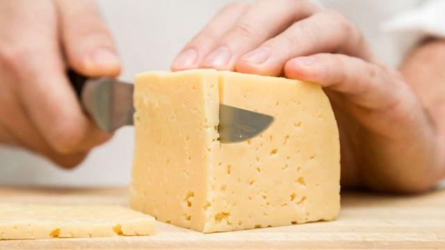 Una persona cortando un trozo de queso