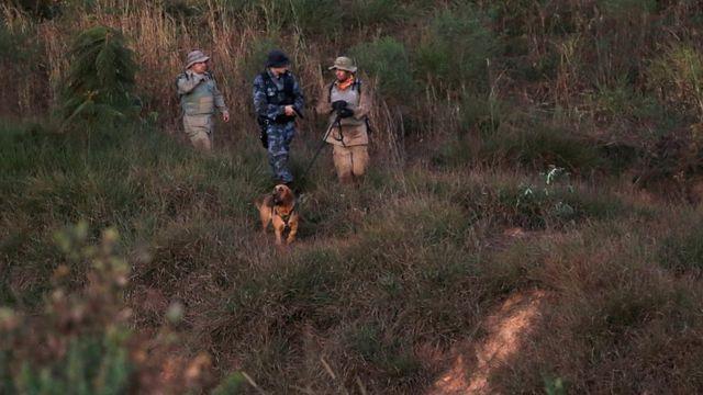Policiais com cachorro farejador durante buscas a Lázaro