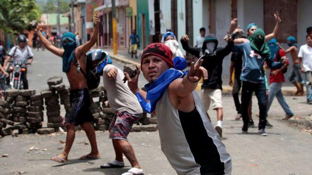 Manifestantes lanzando piedras.