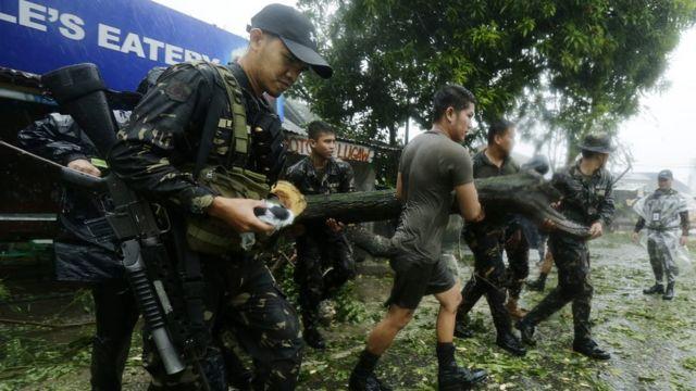 高速道路をふさいでいた倒木などを取り除くフィリピン軍兵士ら(18日)
