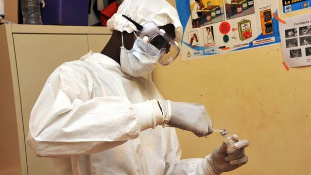 Health worker wey hold injection.