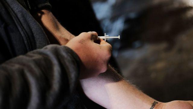 Una persona inyectándose con una jeringa.