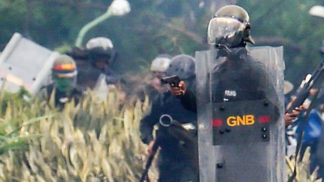 Un funcionario de la Guardia Nacional Bolivariana apunta con un arma de fuego a los manifestantes.