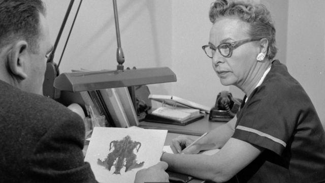 Một nhà tâm lý học thảo luận cách giải thích của một bệnh nhân về hình vết mực, một phương pháp phân tích tâm lý được gọi là thử nghiệm Rorschach