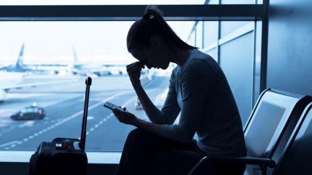 Una mujer en un aeropuerto, viendo su teléfono