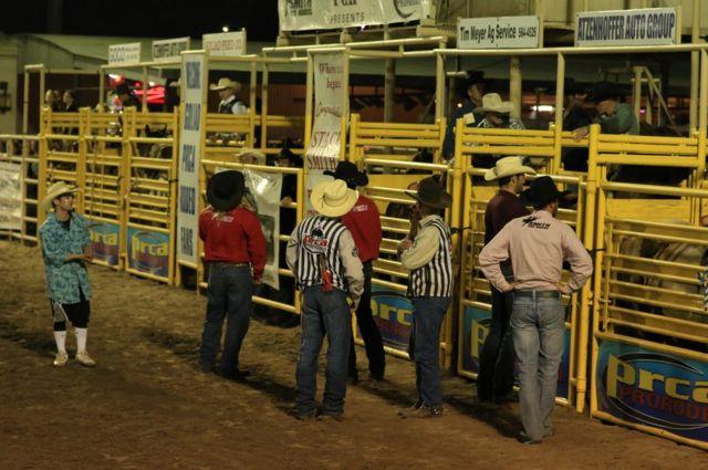 Vaqueros esperan la salida de un jinete montado en un bronco durante un rodeo celebrado en Estados Unidos.
