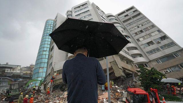 在雨中,一名男子在災場祈禱。