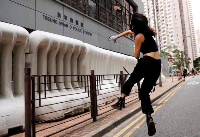 An anti-government protester throws a brick at a police station