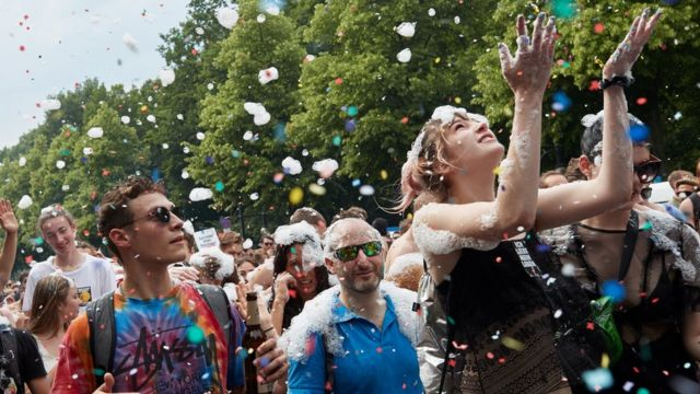 """A woman throws confetti during a protest against a demonstration of the """"Alternative for Germany"""" (AfD) party in Berlin, Germany, 27 May 2018."""