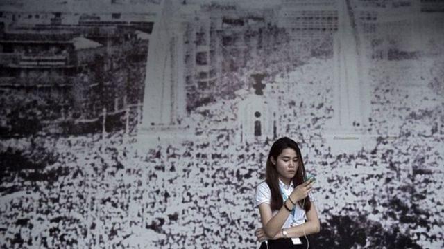นักศึกษาหญิงยืนอยู่หน้าภาพคนจำนวนมากชุมนุมที่อนุสาวรีย์ประชาธิปไตย