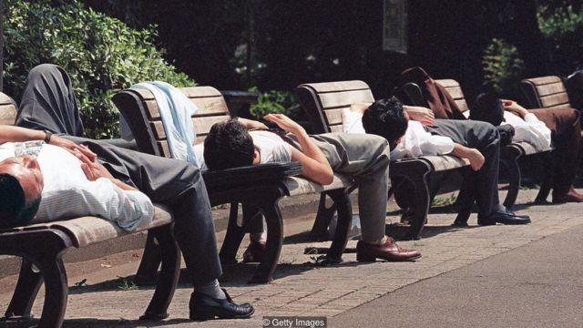 Japoneses dormindo em bancos na rua durante o dia