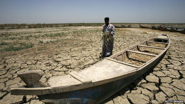 An Iraqi man walks past a canoe sitting on dry, cracked earth in the Chibayish marshes near the southern Iraqi city of Nasiriyah