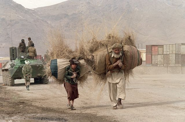 Afghan man and youth haul fire wood on their shoulders past Afghan regular army armoured personnel carrier 15 February 1989 on the Salang Highway near Kabul. Over 100,000 Soviet troops have left the country after nine years's military committment.
