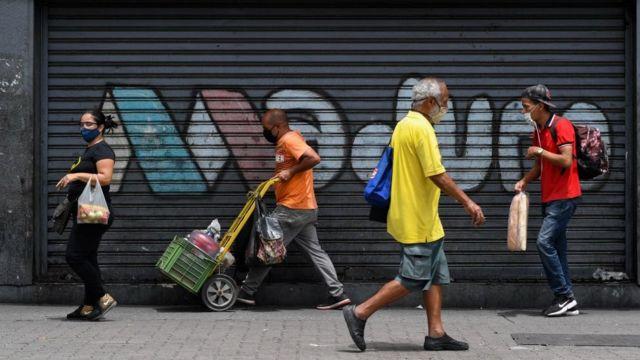 Personas caminan en una calle de Caracas con una pintada de apoyo a Nicolás Maduro.