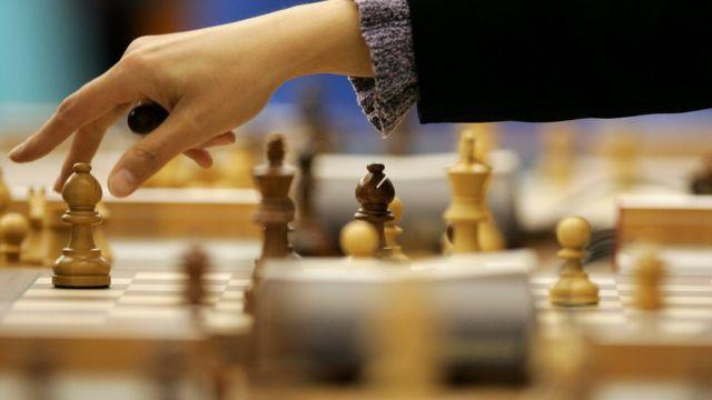 Una mujer jugando ajedrez.