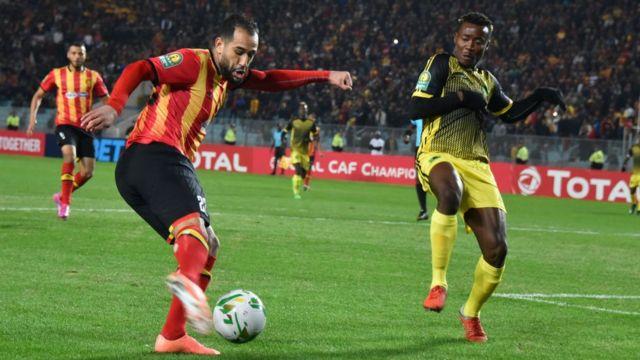 Sameh Derbali, joueur de l'Espérance de Tunis, en maillot rouge et or, joue contre le joueur de l'AS Vita Club, Mumuni Zakaria, vendredi 27 décembre 2019, à Radès.