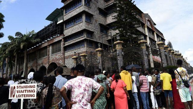 Des habitants et des membres de l'église se rassemblent devant l'entrée principale du siège de l'église synagogue de toutes les nations (SCOA) pour pleurer le décès du pasteur nigérian TB Joshua, dans le district d'Ikotun à Lagos, le 6 juin 2021.