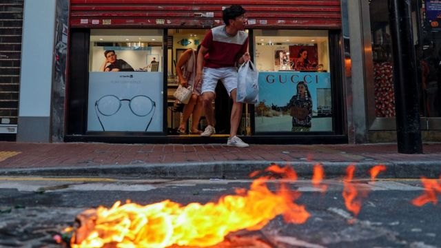 "A customer leaves a shop during a protest march billed as a global ""emergency call"" for autonomy, in Hong Kong."